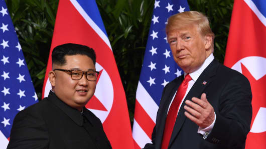 US President Donald Trump (R) gestures as he meets with North Korea's leader Kim Jong Un (L) at the start of their historic US-North Korea summit, at the Capella Hotel on Sentosa island in Singapore on June 12, 2018.