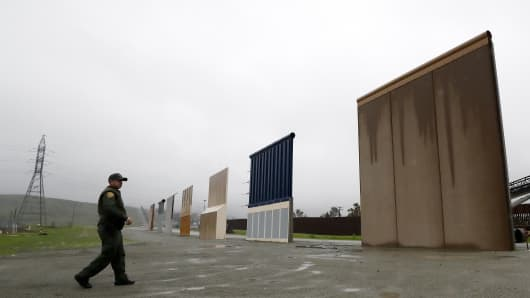Border Patrol agent Vincent Pirro walks towards prototypes for a border wall Tuesday, Feb. 5, 2019, in San Diego.