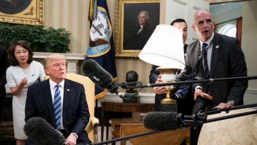 President Donald Trump and Keith Schiller (R) react as a lamp is bumped by press before a meeting with South Korea'ss President Moon Jae-in in the Oval Office of the White House June 30, 2017 in Washington, DC.