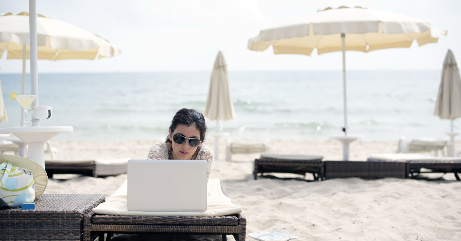 Business woman using computer on the beach