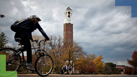 A student rides a bicycle past the bell tower on the campus of Purdue University in West Lafayette, Indiana.