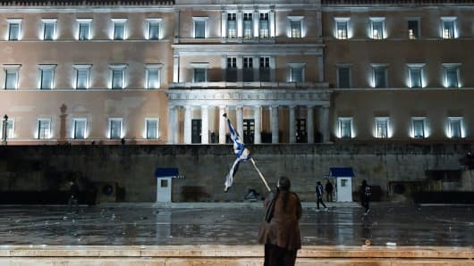 A woman waves a Greek national flag under the rain in front of the Greek Parliament in Athens.