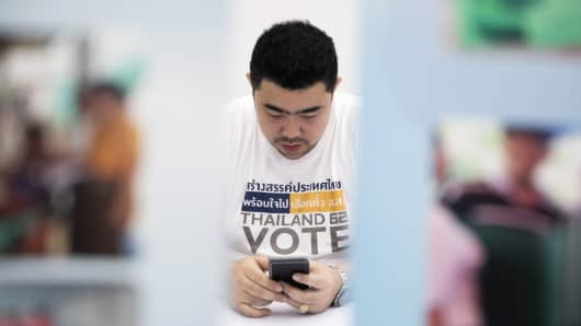 A man wearing a Thailand Vote shirt uses a smartphone at the office of the Election Commission in Bangkok on Feb. 8, 2019