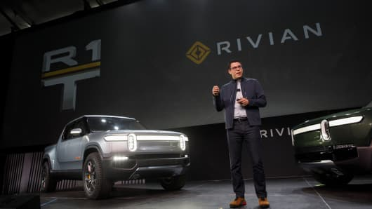 RJ Scaringe, founder and chief executive officer of Rivian Automotive Inc., unveils the R1T electric pickup truck, left, and R1S electric sports utility vehicle (SUV) during a reveal event at AutoMobility LA ahead of the Los Angeles Auto Show in Los Angeles, California.