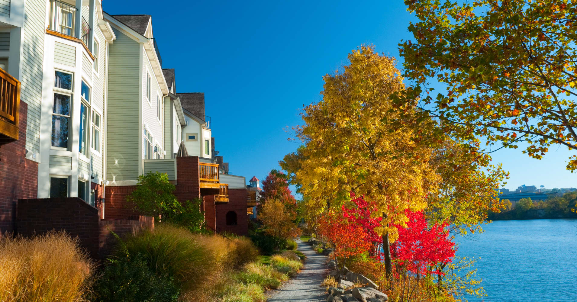 Houses, a pathway, the Allegheny River, and Autumn trees in Washington's Landing in Pittsburgh.