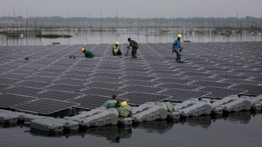 Chinese workers walk on a section of the world's largest floating solar farm project during construction. The lake was created by a collapsed and flooded coal mine in Huainan, Anhui province, China.
