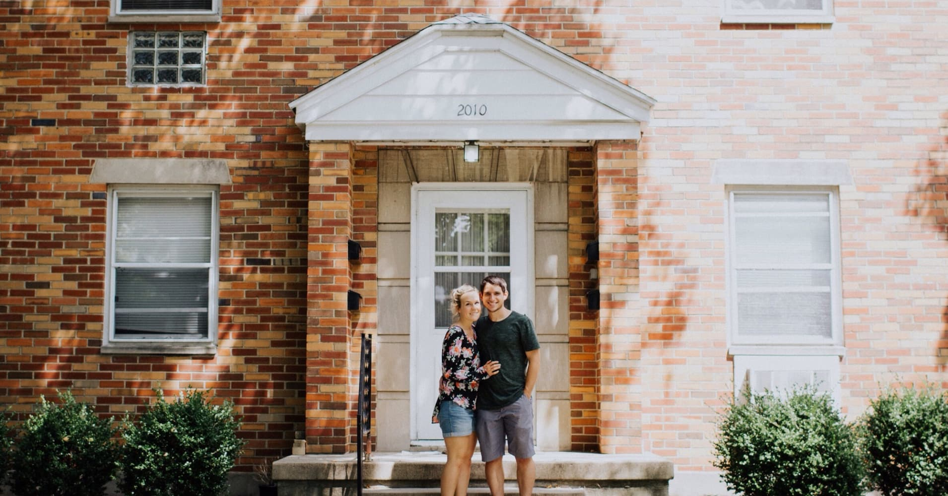 A couple pose in front of a house.