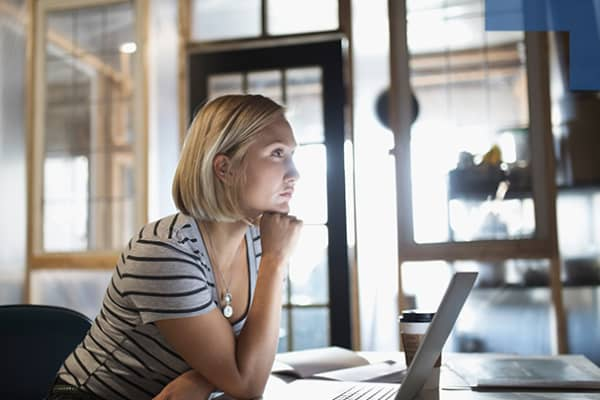 Pensive, focused woman working at laptop in office