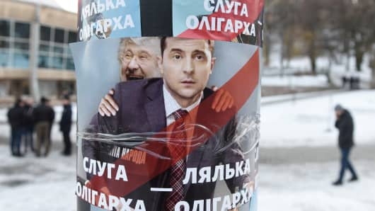 A picture taken on February 8, 2019 shows people walking by placards depicting Ukrainian entertainer and presidential candidate Volodymyr Zelensky and oligarch Ihor Kolomoyskyi, looking out from his back, and reading 'Servant of oligarch, doll of oligarch' is seen glued prior to Zelensky performance in western Ukrainian city of Lviv on February 8, 2019.