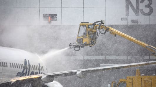 Airport personnel work to de-ice an Alaska Air plane during snowfall at the Seattle-Tacoma International Airport (SEA) in Seattle, Washington, U.S., on Monday, Feb. 11, 2019.