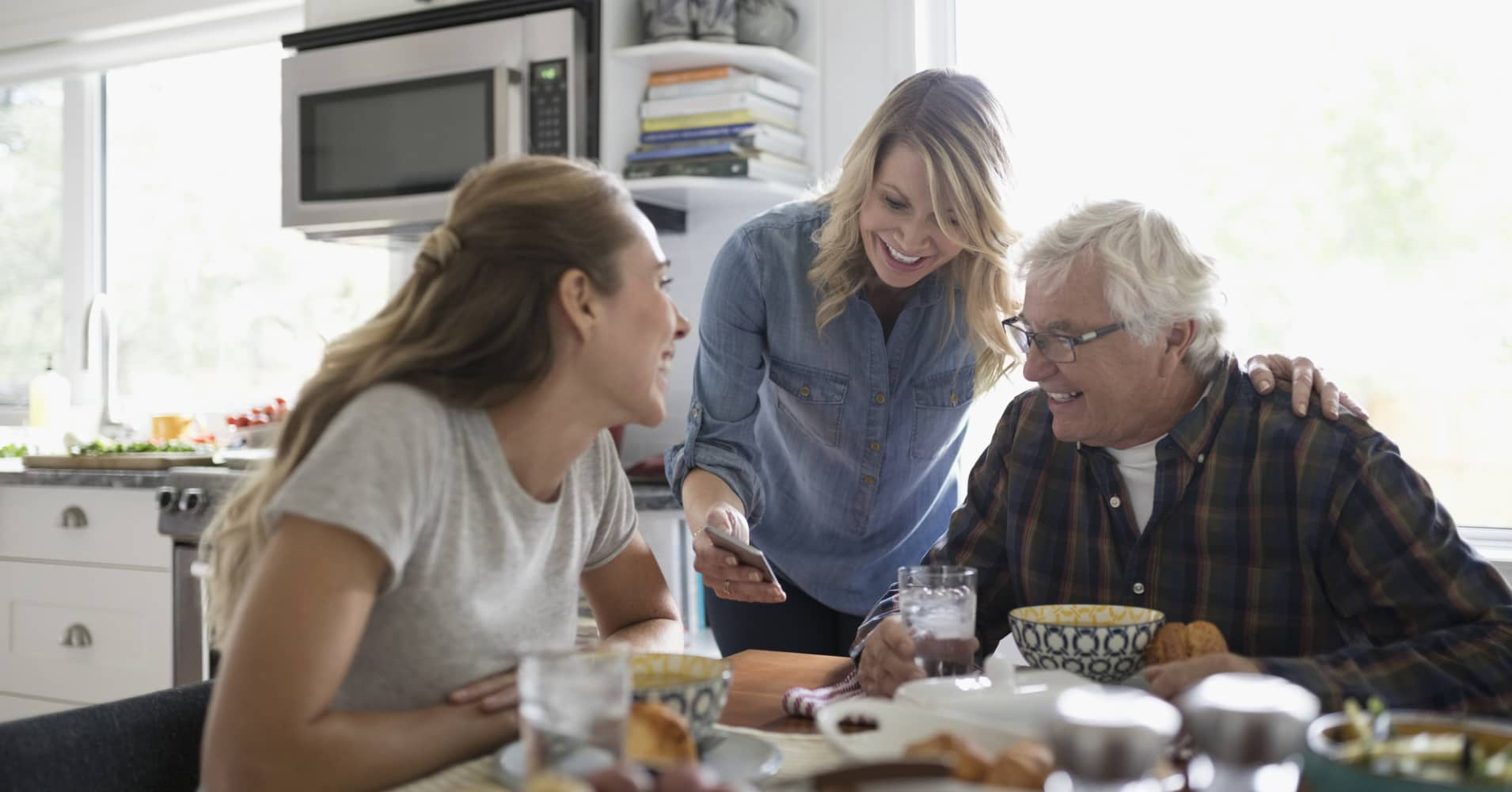 Smiling daughters and senior father using smart phone, eating at kitchen table