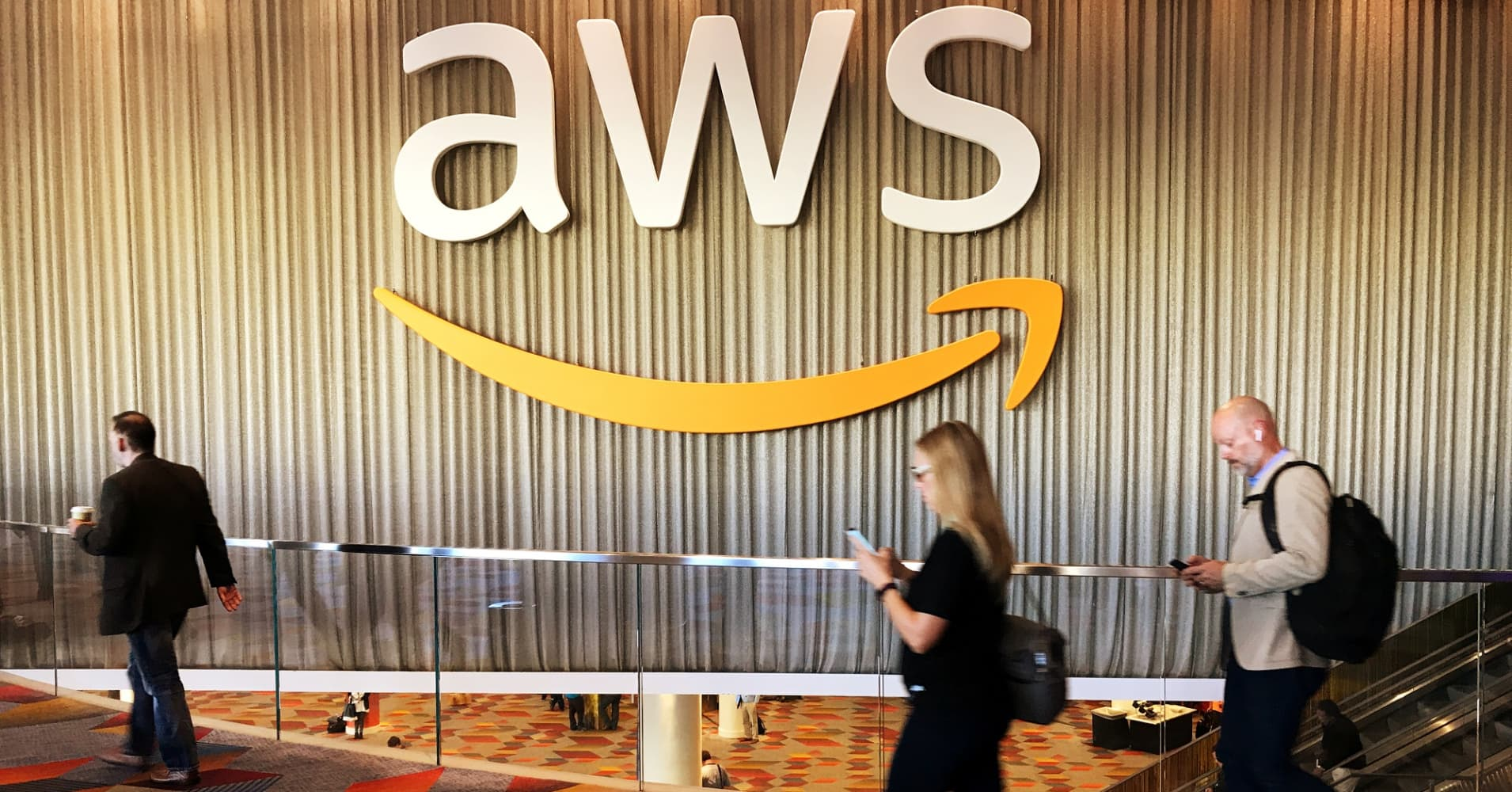 Attendees at Amazon.com Inc annual cloud computing conference walk past the Amazon Web Services logo in Las Vegas, Nevada, U.S., November 30, 2017.