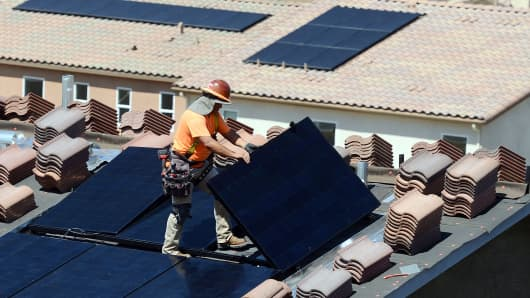 Workers install solar panels on the roofs of homes under construction south of Corona, California. The California Energy Commission in May 2018 adopted new energy building standards requiring solar panels for virtually all new homes built in the state starting in 2020.