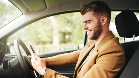 Cropped shot of a handsome young man using the gps navigation on his cellphone while driving
