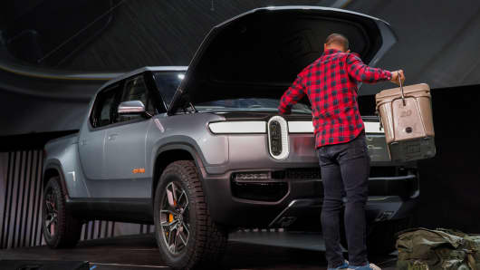 A person places items into the front trunk cargo area of the Rivian Automotive Inc R1T electric pickup truck during a demonstration at a reveal event at AutoMobility LA ahead of the Los Angeles Auto Show.