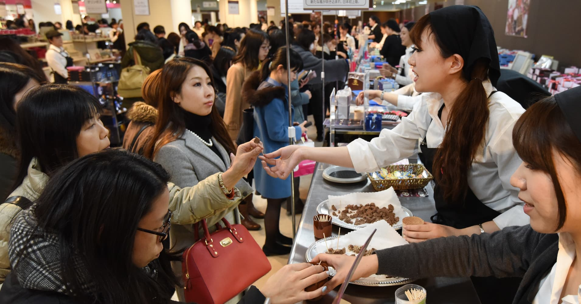 Vendors recommend chocolates to customers at a chocolate counters at the Printemps department store in Tokyo on Feb. 9, 2016, before Valentine's Day on Feb. 14. Elbowing each other in the stampede to buy Valentine's Day chocolate for the men in their lives, Japanese women brought stores to a standstill.