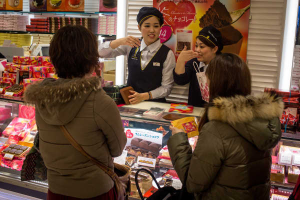 Sales staff discuss specialty chocolates with shoppers at a chocolate store on Feb. 12, 2015 in Tokyo, Japan. On Valentine's Day, Japanese women are expected to give chocolates to men. The chocolate giving tradition in Japan has created a booming business with the month leading up to Feb. 14 sometimes accounting for approximately 50 percent of a confectionery companies annual sales.