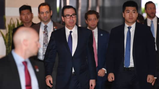 US Treasury Secretary Steven Mnuchin (C) leaves a hotel with members of his negotiation team on the way to high-level trade talks in Beijing on February 14, 2019.