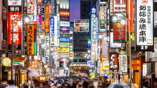 Crowds walk through Tokyo, Japan at night.
