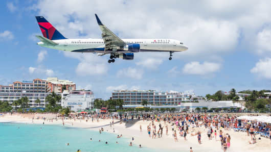 An airplane flying just above beachgoers in Maho Beach as it approaches the landing strip in St. Maarten, 30 March 2016.