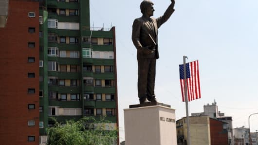 A US flag is placed next to the statue of former US President Bill Clinton in Pristina, Kosovo, on July 4, 2012 to celebrate the US Independence Day.