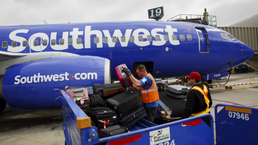 Ground Operations Officers Load Luggage on Southwest Airlines Co. Boeing Co. 737 on the John Wayne Airport (SNA) in Santa Ana, CA, USA, on Thursday, April 14, 2016.