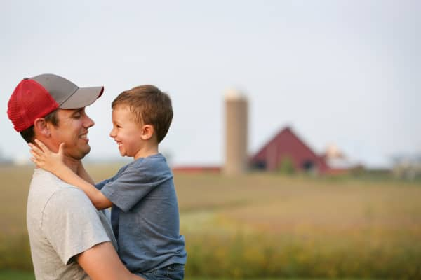 A father and son hug each other on their family farm in Mediapolis, Iowa.