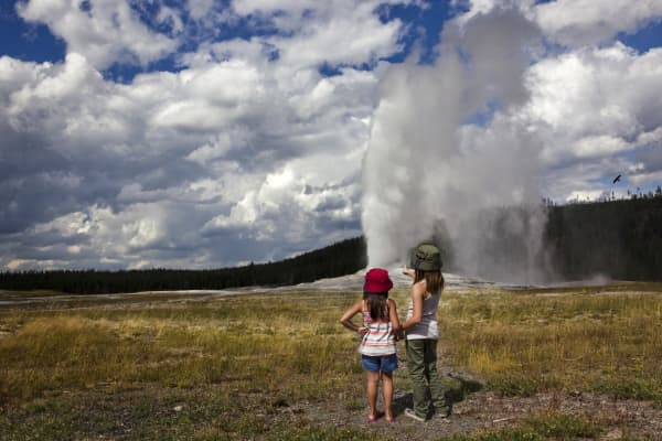 Two girls watch Old Faithful, a geyser located in Yellowstone National Park in Wyoming.
