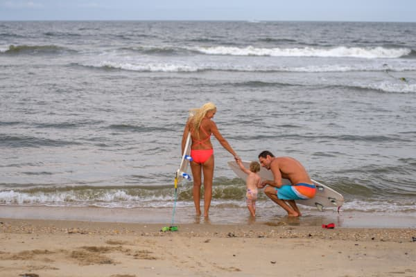 A surfing couple try to coax their toddler in the water at Asbury Park, New Jersey.
