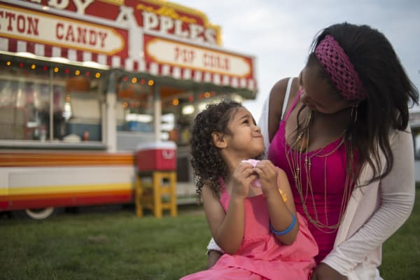A child and her mother share cotton candy at a fairground in Ohio.