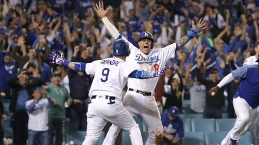 Manny Machado #8 and Yasmani Grandal #9 of the Los Angeles Dodgers celebrate after Machado scored the winning run of Game Four of the National League Championship Series against the Milwaukee Brewers on October 16, 2018 in Los Angeles, California.