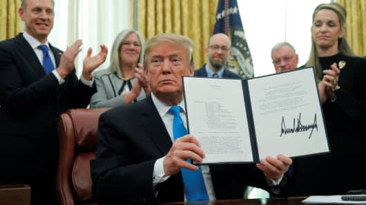 "President Donald Trump displays the ""Space Policy Directive 4"" after signing the directive to establish a Space Force as the sixth branch of the Armed Forces in the Oval Office at the White House in Washington, U.S., February 19, 2019."