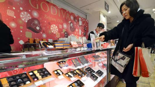 A Japanese woman buys chocolate of Belgium's famous brand Godiva at Tokyo's Takashimaya department store.