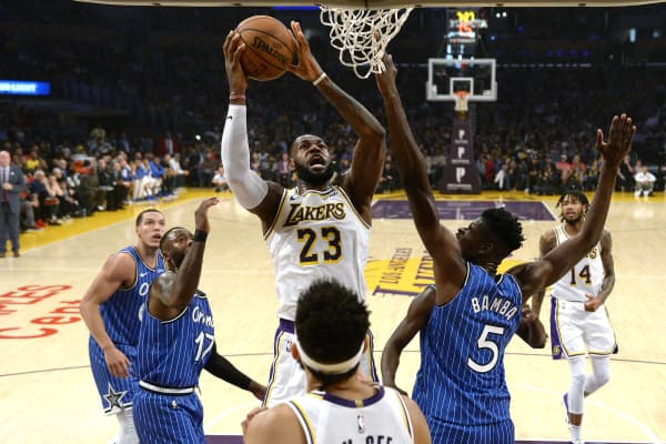 LeBron James #23 of the Los Angeles Lakers scores a basket and gets fouled by Mo Bamba #5 of the Orlando Magic during the first half at Staples Center on November 25, 2018 in Los Angeles, California.