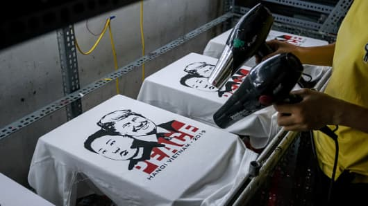 A worker at the t-shirt store of Truong Thanh Duc dry the newly printed t-shirts with the portraits of U.S. President Donald Trump and North Korean leader Kim Jong Un on February 21, 2019 in Hanoi, Vietnam.