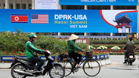 People pass by the International Media Center for the second summit between the Democratic People's Republic of Korea (DPRK) and the United States in Hanoi, Vietnam, on Feb. 24, 2019.