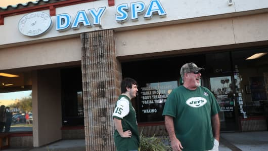 Matthew Gizze (L) and Kevin Brown, both of whom are N.Y. Jets football fans, stop to look at the Orchids of Asia Day Spa where New England Patriots owner Robert Kraft is charged with allegedly soliciting for sex on February 22, 2019 in Jupiter, Florida.