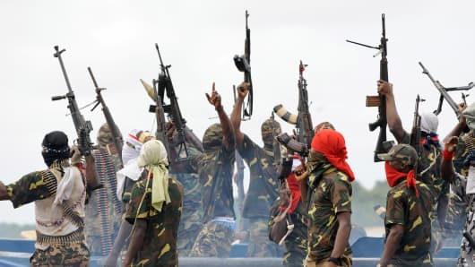 Fighters with the Movement for the Emancipation of the Niger Delta (MEND) raise their riffles to celebrate news of a successful operation by their colleagues against the Nigerian army in the Niger Delta on September 17, 2008.