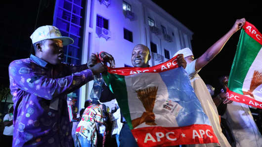 Supporters of the ruling All Progressives Congress (APC) celebrate with party flags in Abuja, Nigeria, after candidate President Mohammadu Buhari was re-elected on February 26, 2019.