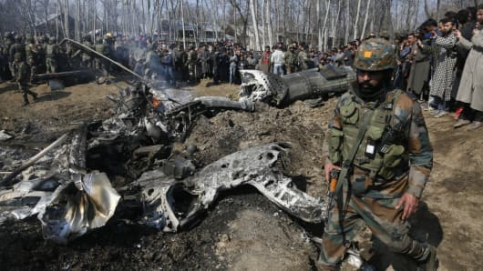 An Indian army solider walks past the wreckage of an Indian aircraft after it crashed in Budgam area, outskirts of Srinagar, Indian controlled Kashmir, Wednesday, Feb.27, 2019.