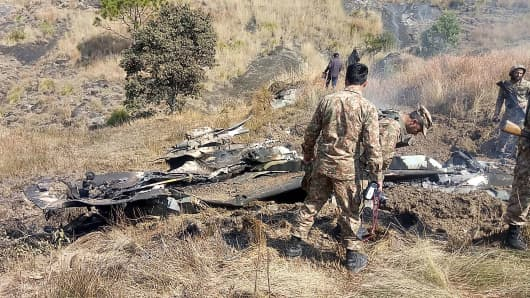 Pakistani soldiers stand next to what Pakistan says is the wreckage of an Indian fighter jet shot down in Pakistan controled Kashmir at Somani area in Bhimbar district near the Line of Control on February 27, 2019.
