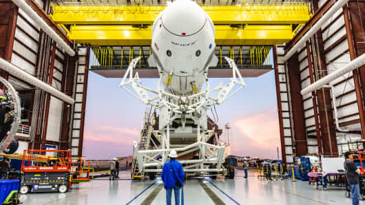 The SpaceX Crew Dragon capsule mounted on the company's Falcon 9 rocket in a hangar at Kennedy Space Center, Florida.