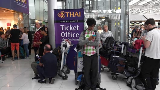 Stranded passengers wait outside the Thai Airways ticket counter at the Suvarnabhumi International Airport in Bangkok on February 28, 2019.
