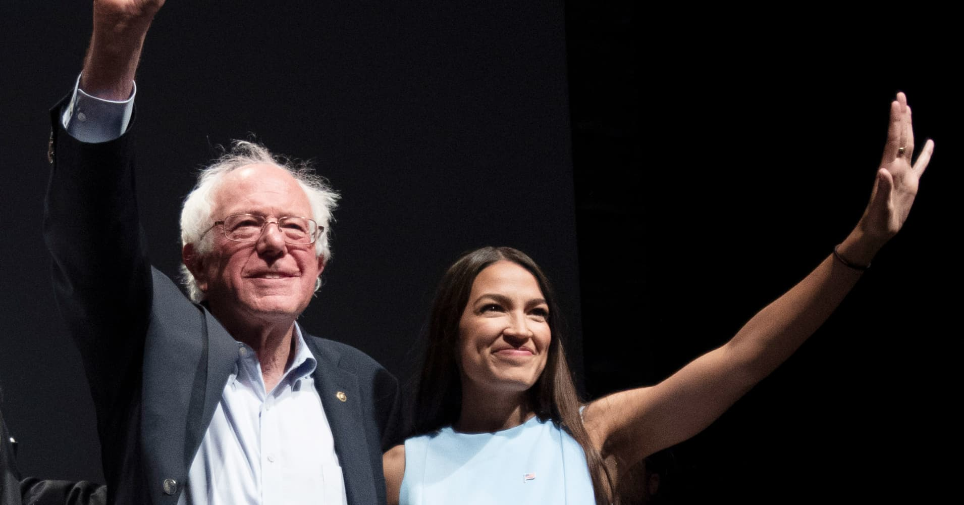 Senator Bernie Sanders and Alexandria Ocasio-Cortez, wave to the crowd at the end of a campaign rally in Wichita, Kansas on July 20, 2018.