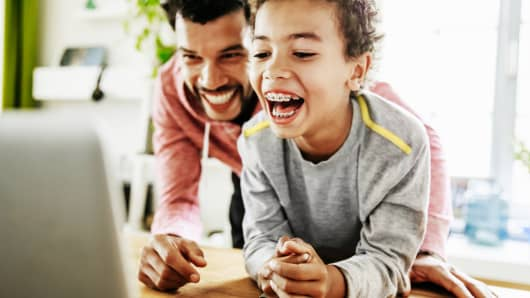 Young Boy Laughing While Watching Computer With Dad