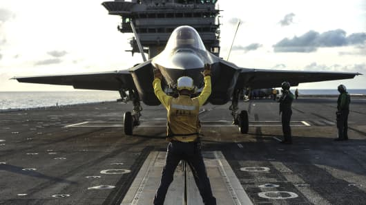 Aviation Boatswain's Mate 3rd Class Juan Cumpston directs an F-35C Lightning II carrier variant to the catapult on the flight deck of the aircraft carrier USS George Washington.