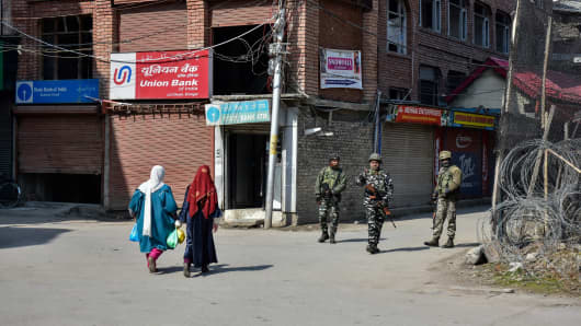 Kashmiri women seen walking past paramilitary troopers during shut down in Srinagar in India-administered Kashmir.