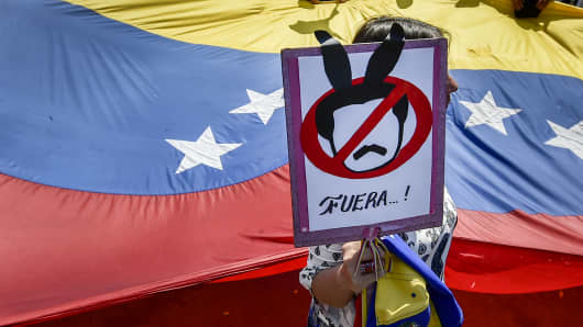 A demonstrator holds a placard as she takes part in a protest of Venezuelans against the government of President Nicolas Maduro at the Simon Bolivar International bridge in Cucuta, Colombia, on the border with Venezuela, on February 15, 2019.