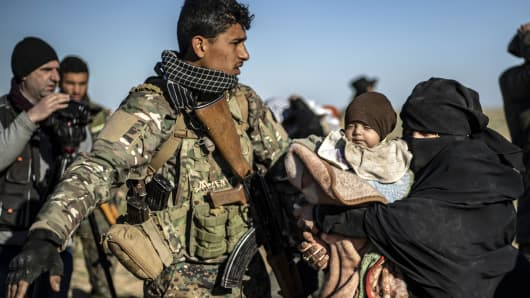 A member of the Kurdish-led Syrian Democratic Forces (SDF) directs a woman carrying a child walking with others as they wait to be searched after leaving the Islamic State (IS) group's last holdout of Baghouz, in the eastern Syrian Deir Ezzor province on March 1, 2019.