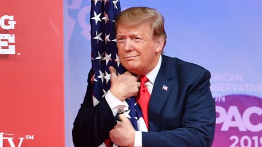 President Donald Trump hugs the US flag as he arrives to speak at the annual Conservative Political Action Conference (CPAC) in National Harbor, Maryland, on March 2, 2019.